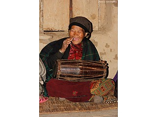 An old women from Aama Samuha playing madal